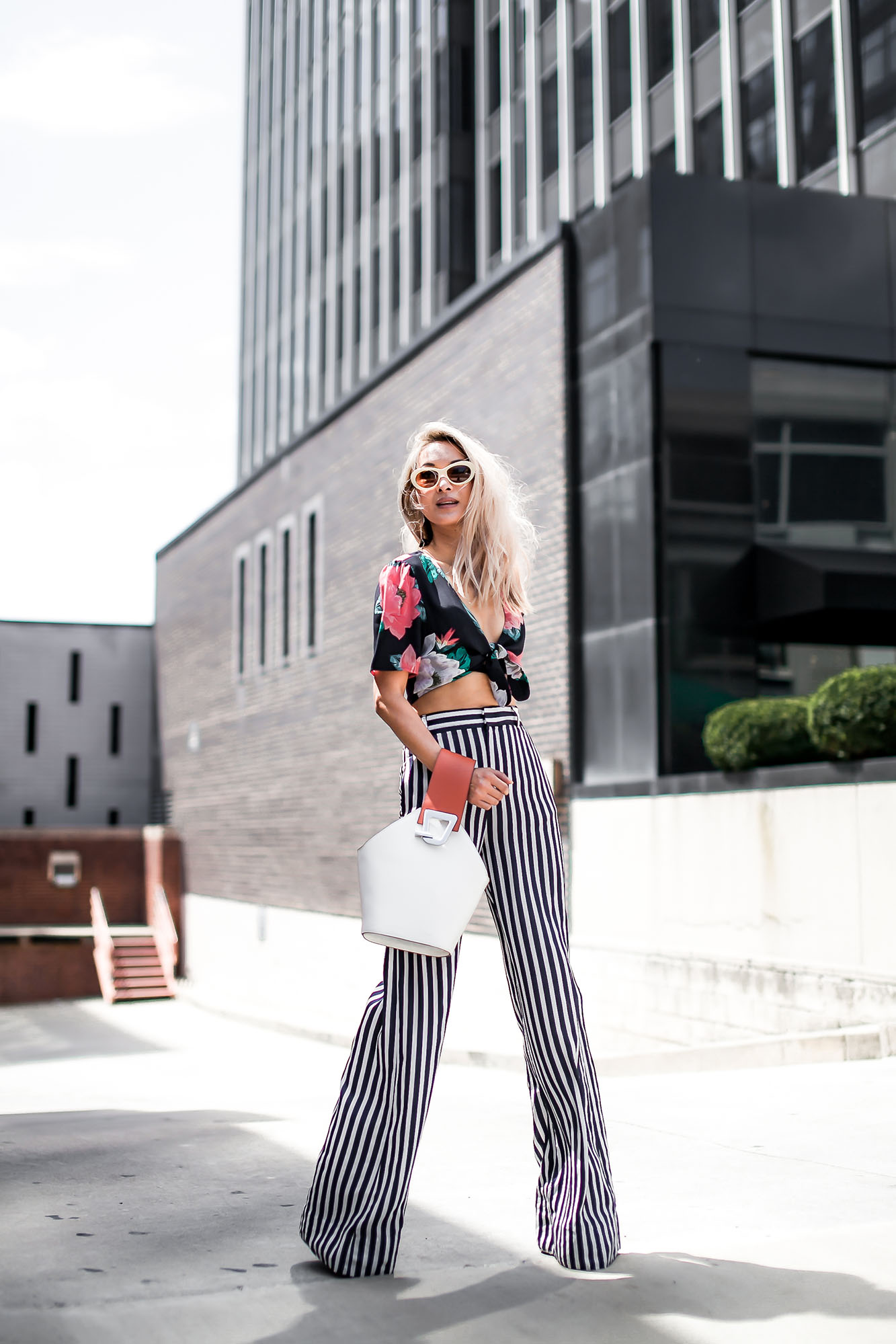 Anchyi Wei of fashion blogger Anchyi Adorned Street Style in Zara floral cropped top, striped pants, retro sunglsses and Danse Lente bucket bag.