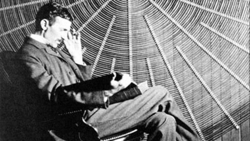 Un'immagine di Nikola Tesla che siede e legge davanti a una spirale a spirale del suo trasformatore ad alta tensione.