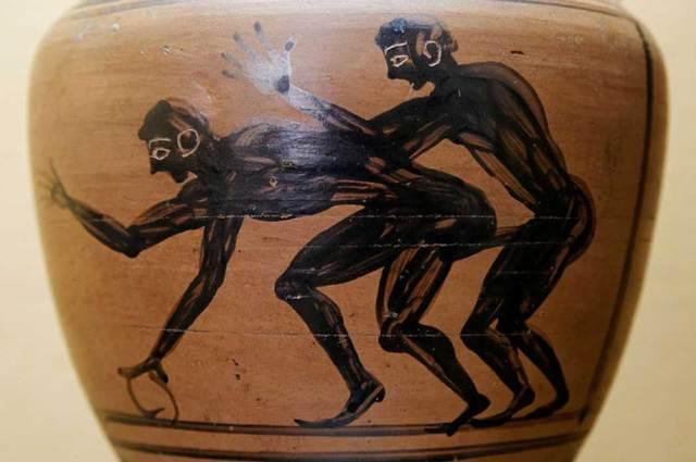Pintura sobre un ánfora en la que se observa a dos jóvenes manteniendo una relación sexual. Curiosamente, uno de ellos empuña un aro. (Dominio público).