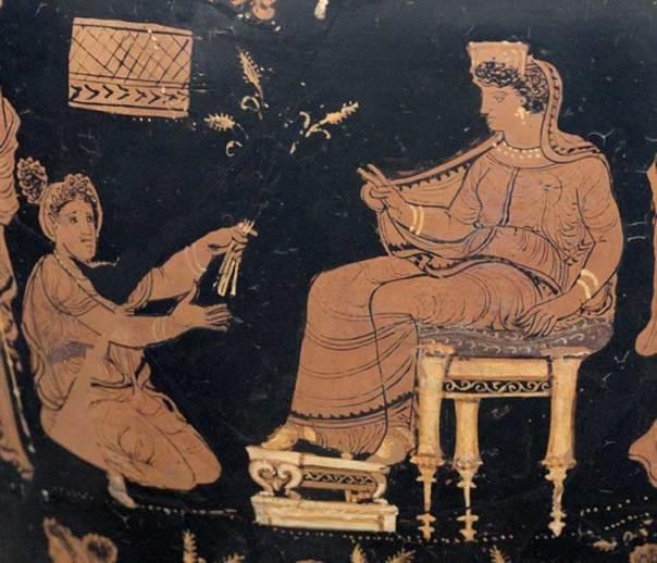 Deméter, sentada en su trono, extiende su mano para bendecir a Metanira, arrodillada ante ella, quien le presenta como ofrenda el trigo trino, un símbolo recurrente de los misterios (Public Domain)