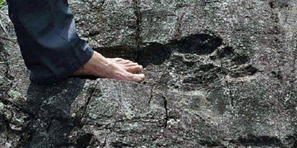 Un hombre se encuentra en lo que parece ser una huella gigante en la roca madre en Pingyin China (Crédito: agencia de noticias Sina)