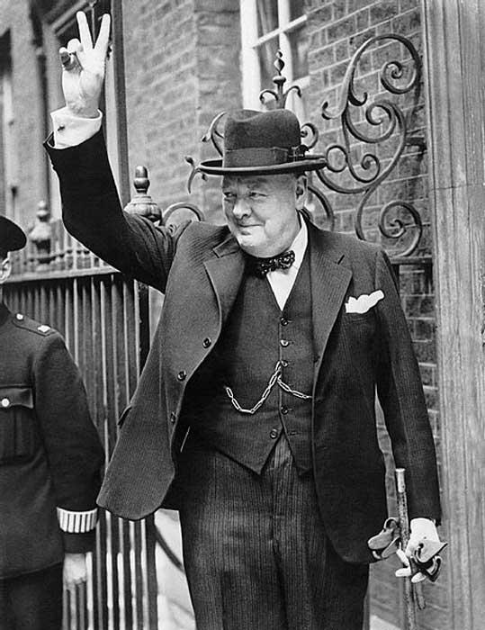 """Winston Churchill in Downing Street dà il suo famoso segno a """"V""""."""