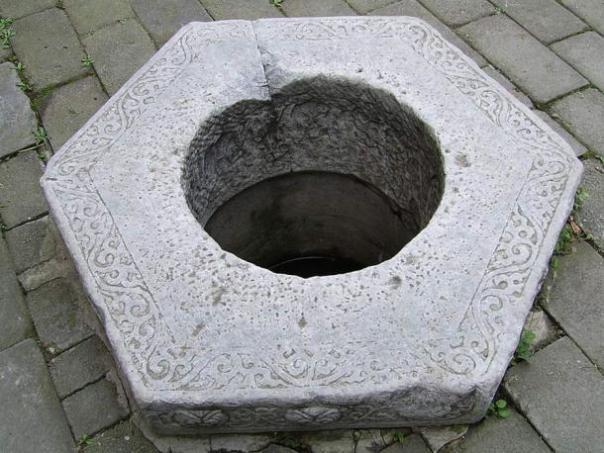 Un chino tallado cabeza del pozo de piedra.