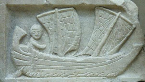 Hombre navegando un corbita, una pequeña embarcación costera con dos mástiles.
