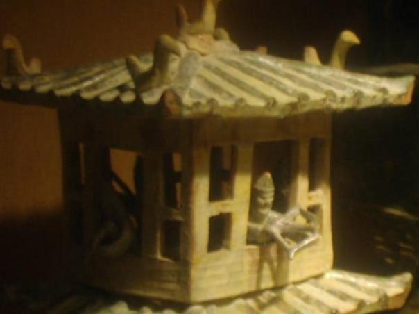 Un guardia miniatura empuñando una ballesta de mano desde el balcón superior de un modelo de torre de vigilancia, de loza vidriada durante la era Han del Este (25-220 dC) de China, desde el Museo Metropolitano de Arte.