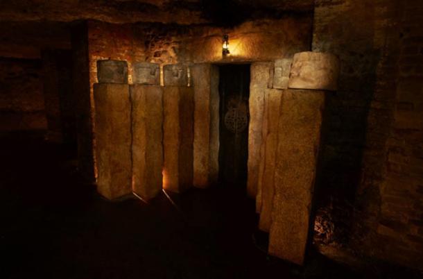 """Porta alla """"Inner Circle"""" contrassegnata con il simbolo di labirinto e fiancheggiato da teste cupi."""