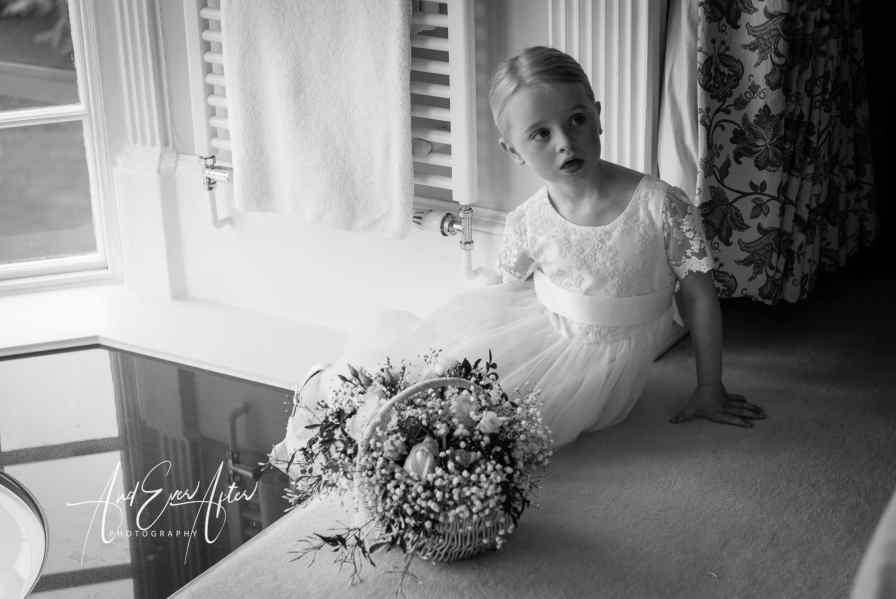 wedding day bridal preparations at Goldsborough Hall flower girl watching as the bride has her make up applied