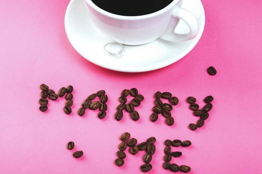 Coffee beans spelling out will you marry me on a saucer