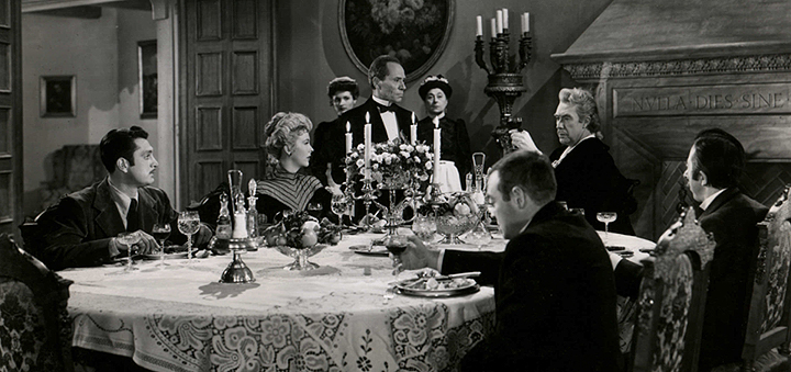 "Left to right: Robert Alda, Andrea King, Patricia Barry, William Edmunds, Belle Mitchell, Peter Lorre, Victor Francen, and David Hoffman in ""The Beast With Five Fingers,"" Warner Bros., 1946."