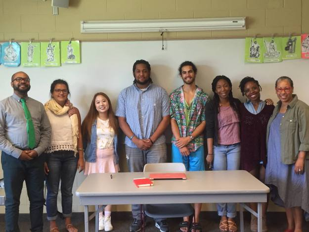 A diverse group of two professors and six college students, all smiling, pose for a group photo, standing in a single row, in a college classroom. In the foreground, there is a desk and chair, and in the background there is a whiteboard.