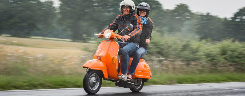 Vespa World Days 2017, zwei lachende Personen auf einer Vespa.