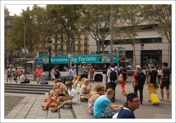 Туристы отдыхают на площади Каталонии.
