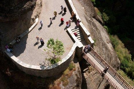 Туристы над пропастью у мостика, ведущего в монастырь Варлаама. Метеоры.
