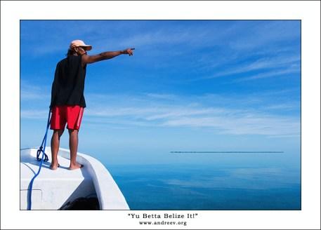 А нырять мы будем в-ооон там! Гид с якорем в руке показывает предполагаемое место ныряния. На горизонте – остров, часть кораллового рифа.