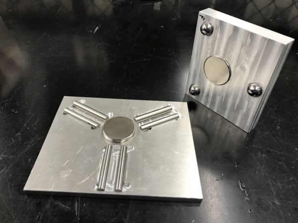 two aluminum plates one with three sets of two dowel pins and the other with three balls, each having a magnet in the center