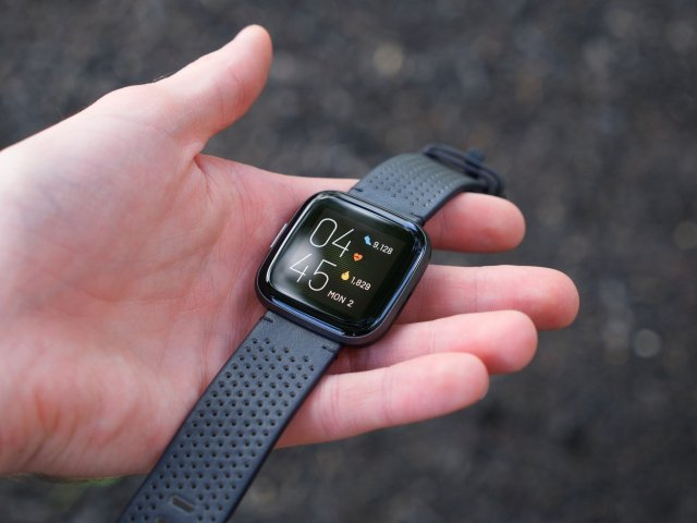 Fitbit Versa 2 with leather band being held