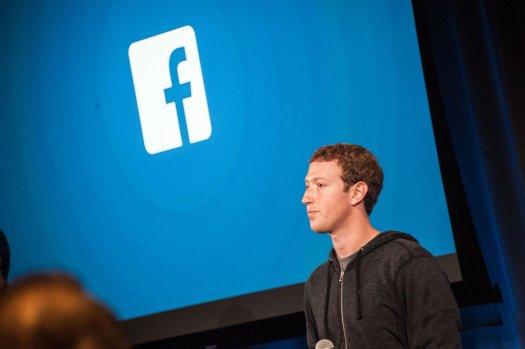 Mark Zuckerberg in front of the Facebook logo