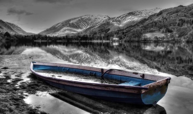 Blue boat on lake. A black and white image enhanced to color the boat in the foreground a subtle blue. The lake mirrors the boat and mountains in the background. A white house nestles on the shore. Taken in the Lake District, a beautiful area of mountains and lakes in Cumbria, UK. © Copyright 2014 Andy Huntley photography