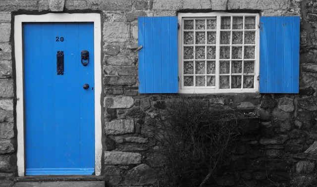 Blue Door. Striking enhanced black and white photograph of a stone country cottage with its wooden door and window shutters picked out in bright blue. © Copyright Andy Huntley photography