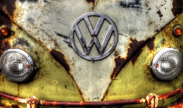 Camper van. Colour photograph showing a section of the front of an iconic Volkswagon camper van. The bodywork is old with rust and interestingly crackled paintwork giving the image its character. The V W logo and grated headlamps would raise a smile of friendliness for which the van is known. © Copyright 2014 Andy Huntley photography