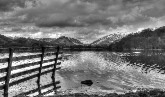 Stunning black and white photograph of a gate edging into a lake. The gate runs from the bottom left of the image echoing the pitch of one of the two mounts forming a v in the centre top third. Gate, mountains and sky are mirrored in the rippling lake surface. The softness of leafy trees on the right contrast with the hard rocky surface of the mountains with their tops lightly covered with snow. The cloud cover, bright white in a few places then encompasses every shade of grey in its bubbling, cotton wool texture. © Copyright 2014 Andy Huntley photography
