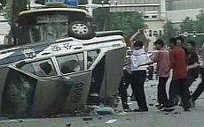 Uighur youths overturn a car during the violence in Urumqi, July 5, 2009