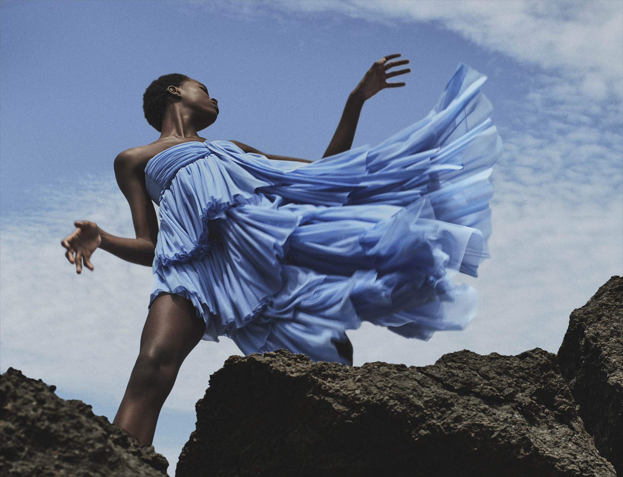 Mujer Hoy fotografía editorial chica piel oscura con vestido vaporoso azul sobre roca