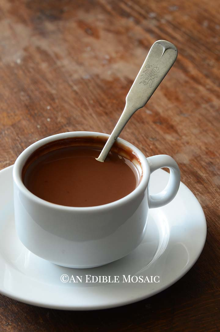Drinking Chocolate (French Hot Chocolate) in White Cup with White Saucer on Wooden Table