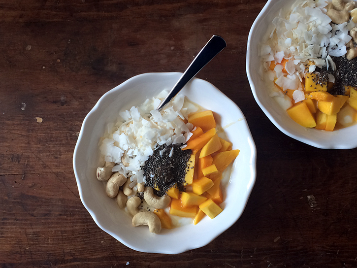 Yogurt with fresh mango, flaked coconut, cashews, chia seeds, and a drizzle of honey.