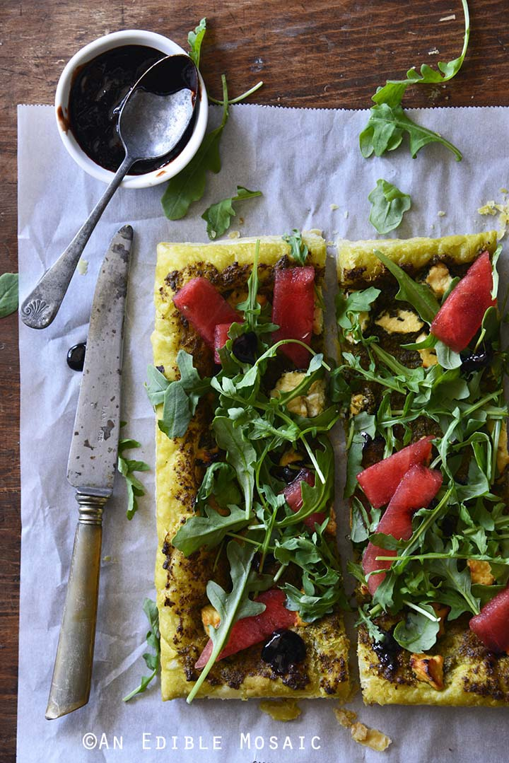 Garlic and Chive Goat Cheese and Pesto Puff Pastry Tart with Arugula, Watermelon, and Strawberry-Balsamic Drizzle Top View, Vertical Orientation
