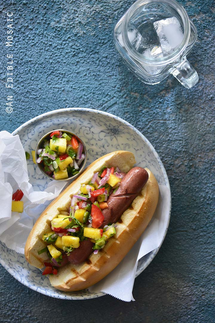 Hot Dogs with Hawaiian-Inspired Pineapple Jalapeno Teriyaki Relish on Blue Background Top View with Water Glass
