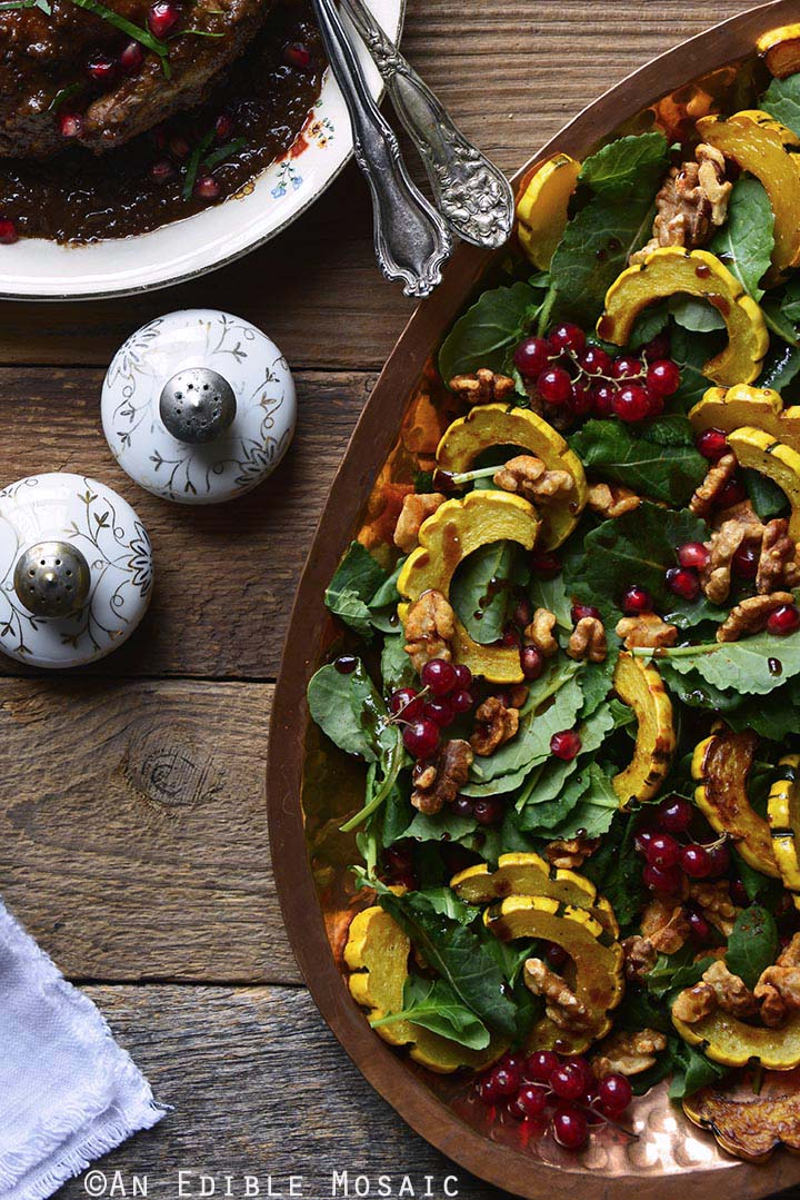 Roasted Winter Squash Salad with Spiced Walnuts, Red Currants, and Pomegranate Balsamic Vinaigrette with Cornish Hens and Decorative Salt and Pepper Shakers on Wooden Table