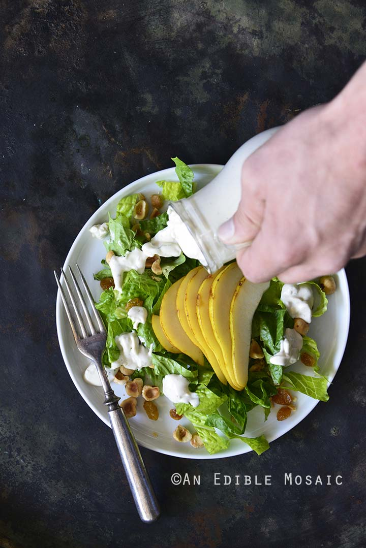 Pouring The Best Creamy Blue Cheese Dressing on Pear Hazelnut Salad