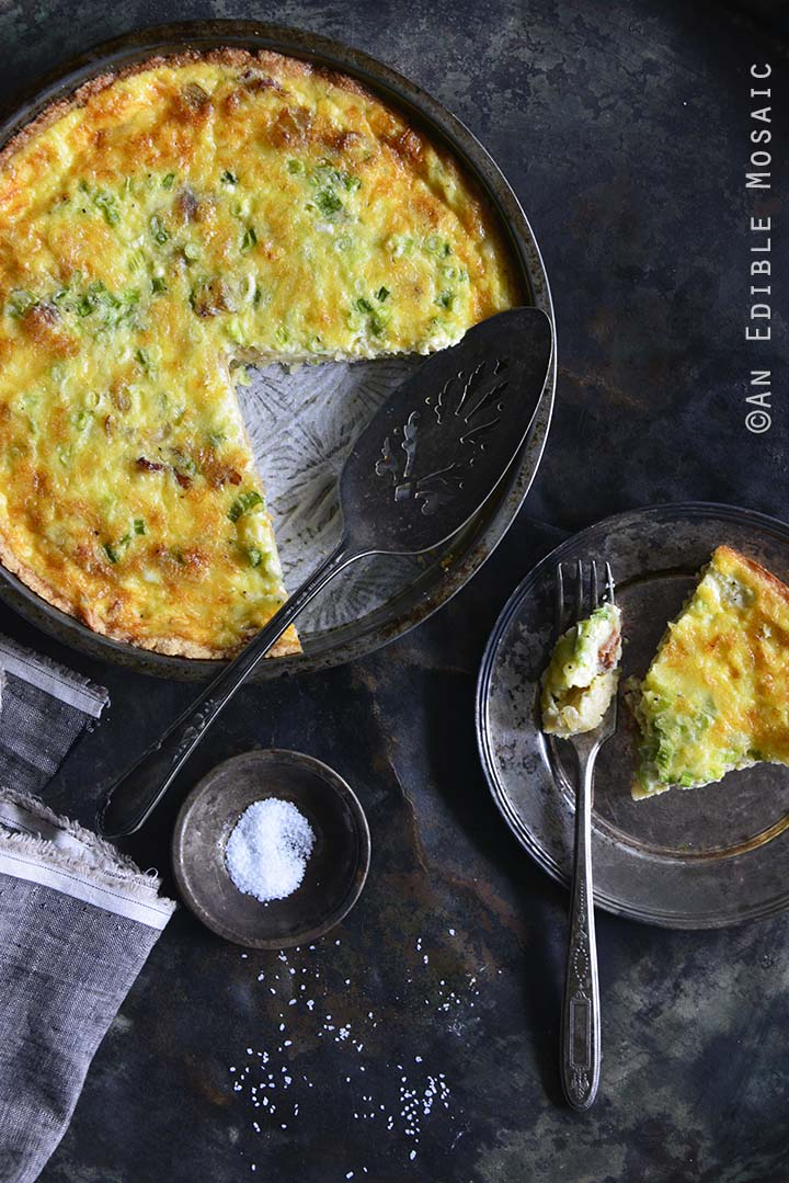 Keto Low Carb Quiche Lorraine in Tart Dish with a Single Serving on a Plate on the Side