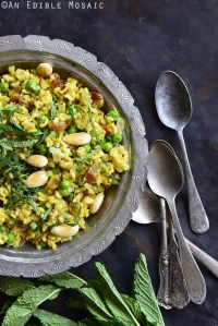 Top View of Indian-Inspired Golden Rice and Green Pea Pilaf with Fresh Mint in Silver Bowl