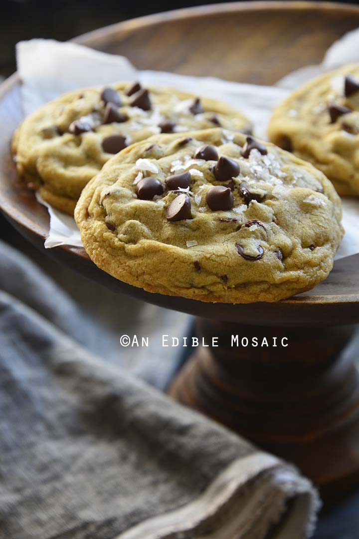 Small Batch Bakery Style Chocolate Chip Cookies on Wooden Pastry Stand with Dark Linen
