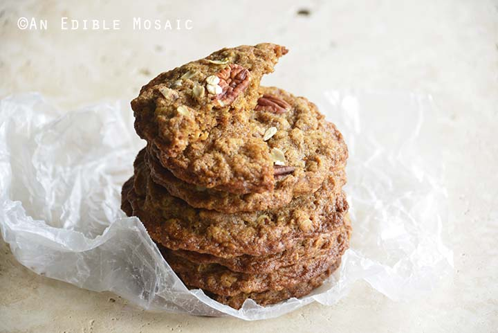 Stack of Chewy Cinnamon Pecan Brown Butter Oatmeal Cookies on Crumpled Wax Paper