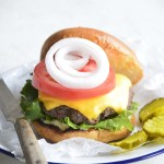 Front View of Cast Iron Burger on Bun with Lettuce Tomato Onion and Pickles on White Plate with Blue Rim