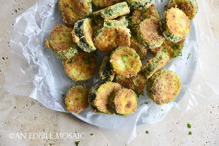 Top View of Keto Crispy Baked Zucchini Slices on White Plate with Wax Paper