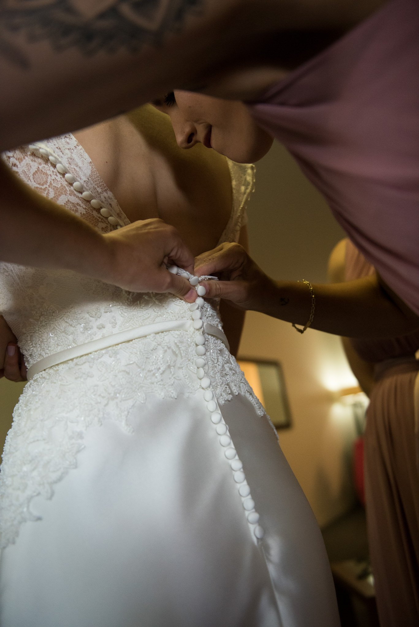 back of wedding dress getting buttoned