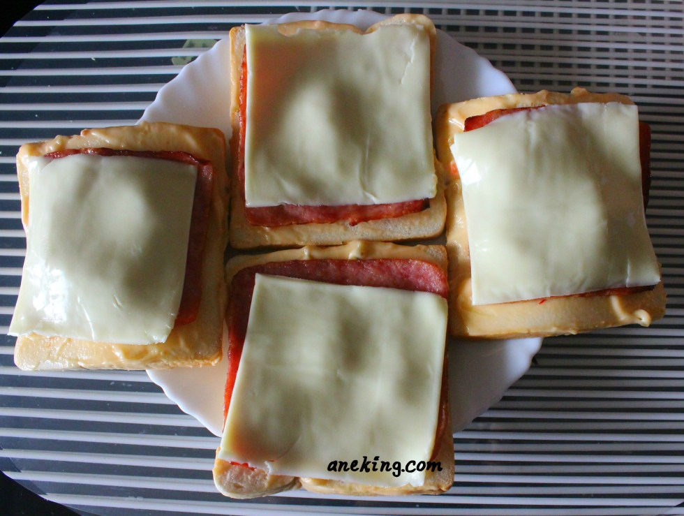 3. Add cheese and ham on top of the sandwich breads with spreads on it.