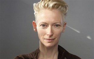 Actress Tilda Swinton is pictured in headshot, barely smiling, with short, backswept, blond hair and intense, blue-gray eyes.