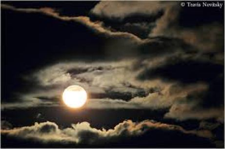 Photograph of a full moon amid passing clouds