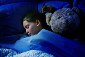Photo shows a young girl in darkened room asleep under a blue blanket with a large teddy bear by her side.