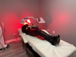 Woman receiving red LED treatment at AnewSkin Medspa