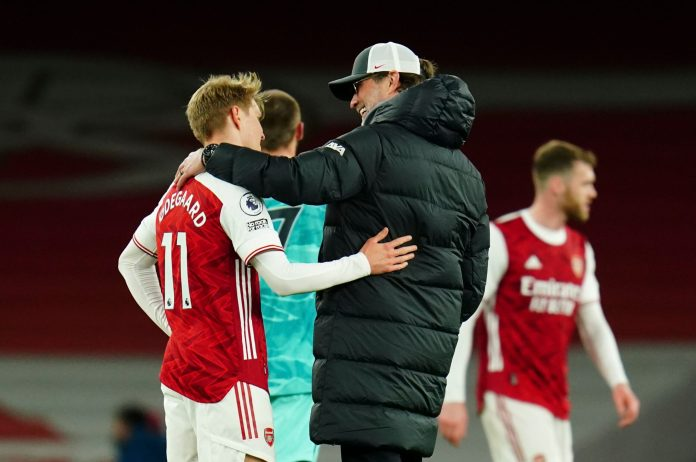 LONDON, ENGLAND - APRIL 03: Martin Odegaard of Arsenal and Liverpool Manager Jurgen Klopp chat after the Premier League match between Arsenal and Liverpool at Emirates Stadium on April 03, 2021 in London, England.