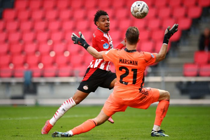 EINDHOVEN, NETHERLANDS - MARCH 14: Donyell Malen of PSV scores his teams first goal past Goalkeeper, Nick Marsman of Feyenoord Rotterdam during the Dutch Eredivisie match between PSV Eindhoven and Feyenoord at Philips Stadion on March 14, 2021 in Eindhoven, Netherlands