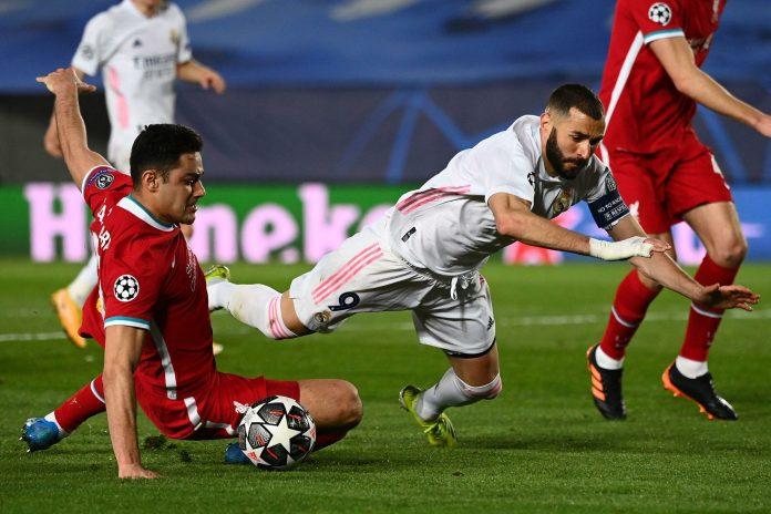 Real Madrid's French forward Karim Benzema (R) is fouled by Liverpool's Turkish defender Ozan Kabak during the UEFA Champions League first leg quarter-final football match between Real Madrid and Liverpool at the Alfredo di Stefano stadium in Valdebebas in the outskirts of Madrid on April 6, 2021.