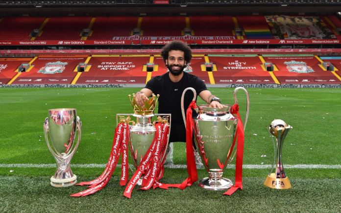 Mohamed Salah poses with the silverware he has won with Liverpool at Anfield, Liverpolol, United Kingdom.