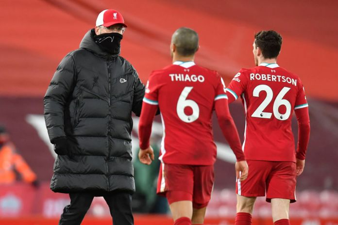 Liverpool's German manager Jurgen Klopp (L) wearing a protective face covering to combat the spread of the coronavirus, congratulates Liverpool's Spanish midfielder Thiago Alcantara (C) and Liverpool's Scottish defender Andrew Robertson (R) after the English Premier League football match between Liverpool and Manchester United at Anfield in Liverpool, north west England on January 17, 2021. - The game finished 0-0. (Photo by Paul ELLIS / POOL / AFP) / RESTRICTED TO EDITORIAL USE. No use with unauthorized audio, video, data, fixture lists, club/league logos or 'live' services. Online in-match use limited to 120 images. An additional 40 images may be used in extra time. No video emulation. Social media in-match use limited to 120 images. An additional 40 images may be used in extra time. No use in betting publications, games or single club/league/player publications. / (Photo by PAUL ELLIS/POOL/AFP via Getty Images)